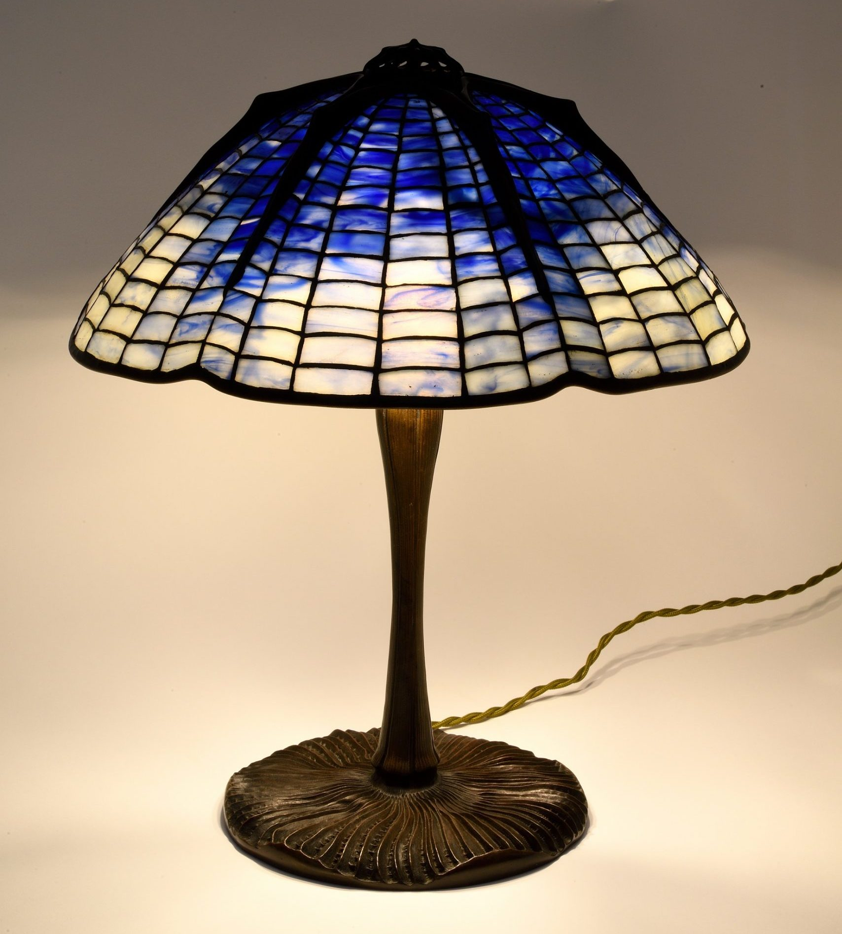 Tiffany lamp with an upturned mushroom base and blue spiderweb design lampshade